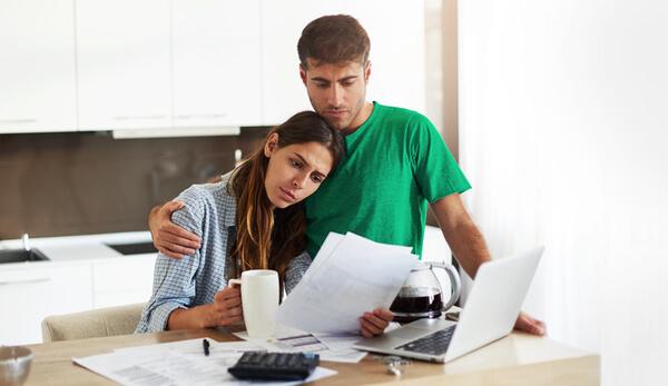Casal avaliando e conversando sobre dívidas em família