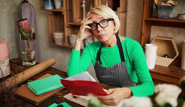 Mulher pensando como se livrar das dívidas da sua empresa e manter as contas em dia